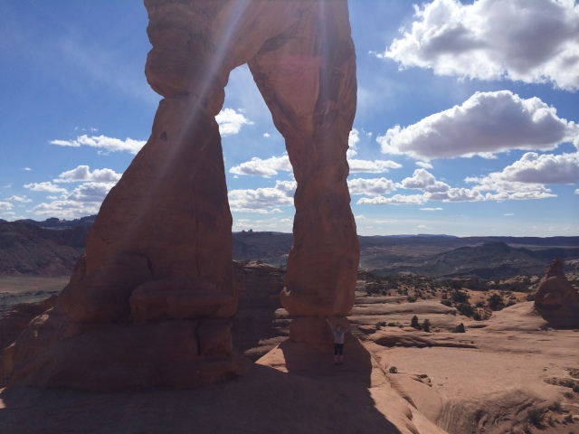 Me standing under Delicate Arch (and avoiding the steep drop off!)