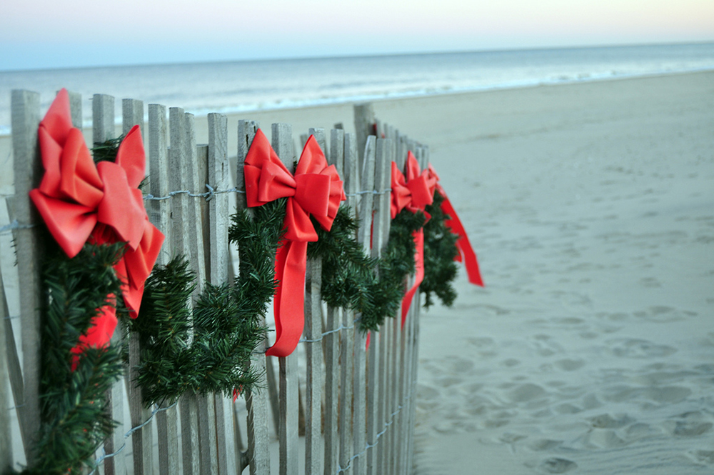 Red bows and evergreen bows on a fence on a beach.